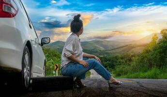 bela jovem sentada perto de um carro pedindo ajuda na via pública em uma área de floresta com uma montanha e o céu ao fundo foto
