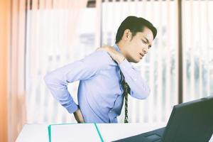 homem asiático com dor nas costas no escritório foto