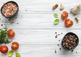 tomate manjericão e pimenta com alho em fundo branco de madeira foto