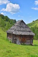 velha casa de madeira solitária em uma colina de montanha com grama verde contra o céu azul foto