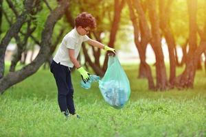menino catando lixo em uma floresta de primavera ao pôr do sol foto