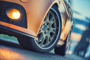 close-up da roda dianteira do carro esporte na estrada de asfalto ao anoitecer foto