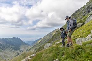 pai e filho no topo da montanha caminhando com mochilas em dia de sol foto