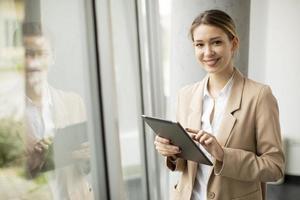 mulher segurando tablet em escritório moderno foto