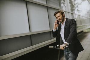 homem de scooter falando ao telefone foto