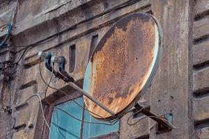 Antena parabólica enferrujada em uma casa velha foto