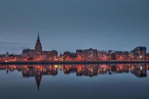 vista noturna na ribeira iluminada com reflexo no rio em riga foto