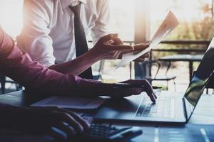 discussões de pesquisa econômica, equipe de negócios analisando tabelas de renda e gráficos para planejar o conceito de marketing com o uso de laptop e calculadora para análise. foto