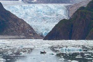 homem em um barco em frente à geleira Sawyer nos fiordes de Tracy Arms no Alasca, Estados Unidos foto