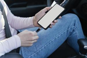 mulher carregando seu telefone no carro foto