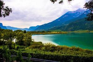 lago caldaro cercado pelas montanhas em bolzano, itália foto