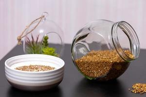 alimentação saudável mingau de trigo sarraceno em um prato cheio de leite em uma mesa escura com verduras foto