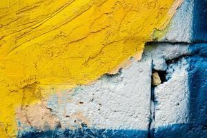 cimento amarelo velho e parede de tijolo azul foto