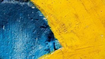 velho muro de cimento azul e amarelo foto