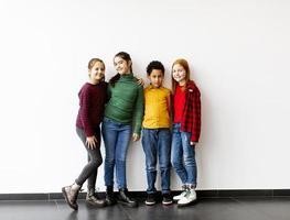 retrato de crianças fofas em jeans olhando para a câmera e sorrindo em pé contra uma parede branca foto
