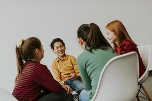 retrato de crianças fofas em jeans conversando e sentando em cadeiras contra uma parede branca foto
