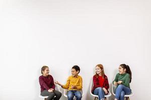 retrato de crianças fofas em jeans, sentadas em cadeiras contra uma parede branca foto