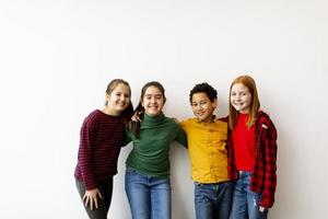 retrato de crianças fofas em jeans olhando para a câmera, sorrindo e encostadas na parede branca foto