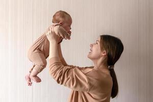 alegre linda jovem segurando uma menina nas mãos e olhando para ela com amor em casa foto
