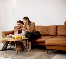 mulher e homem jovem usando laptop para pagamento on-line enquanto estão sentados no sofá em casa foto