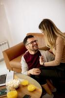 mulher jovem e homem jovem usando laptop enquanto está sentado no sofá em casa foto