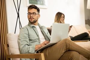 jovem usando laptop em casa foto