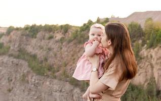 mãe segura uma criança nos braços e beija-a suavemente na bochecha ao ar livre foto