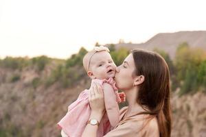 mãe segura uma criança nos braços e o beija suavemente na bochecha ao ar livre foto