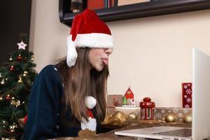menina com chapéu de Papai Noel usando laptop para videochamada para amigos e pais foto