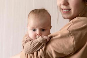 uma jovem mãe segura uma menina de 3 meses foto