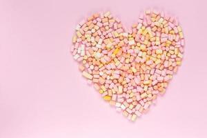 vista superior dos marshmallows multicoloridos em forma de coração em um fundo rosa monocromático foto
