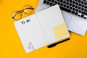 área de trabalho da mesa do escritório em casa com laptop em fundo amarelo foto