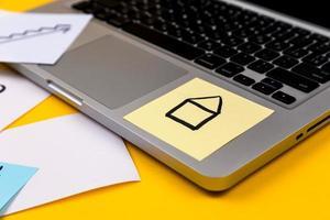 área de trabalho da mesa do escritório em casa com laptop e adesivo de papel no fundo amarelo foto