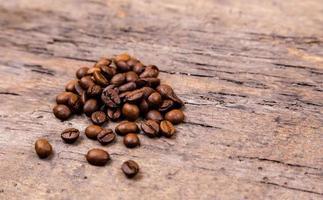 grãos de café aromáticos na mesa de madeira branca foto