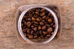 grãos de café em uma jarra de vidro sobre um fundo de madeira foto