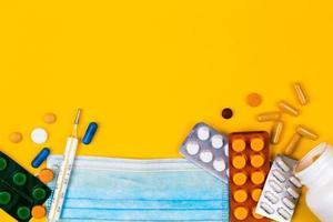 máscara médica protetora em fundo amarelo rodeada de pílulas coloridas foto