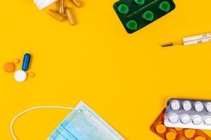máscara facial de proteção médica de algodão azul sobre fundo de papel amarelo com comprimidos foto
