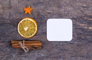 uma pilha de paus de canela, laranja seca e estrelas de tangerina em uma velha mesa de madeira em forma de árvore de Natal foto