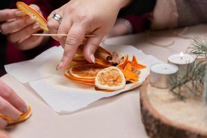 Mulheres fazendo enfeites à mão com laranjas secas foto