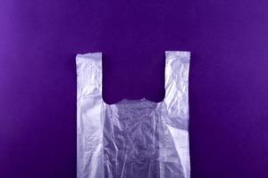 sacola de compras de plástico rasgada em fundo roxo foto