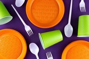 coleta de lixo de plástico laranja verde em fundo roxo foto