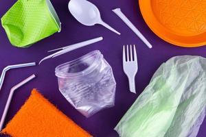 embalagem de produtos de plástico laranja, branco e verde em fundo roxo foto