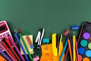 material de escritório escolar em uma mesa de fundo verde com espaço de cópia foto