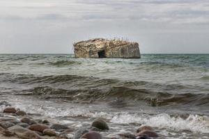 antigo bunker alemão é lavado no mar da costa do Báltico foto