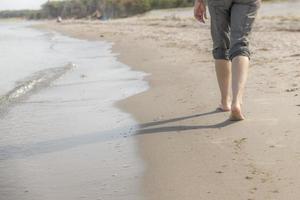 mulher caminha à beira-mar com áreas desfocadas foto
