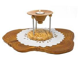 Castiçal de madeira com várias partes e vela acesa em uma placa de madeira escura foto