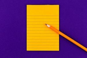 folha de papel laranja e lápis em fundo roxo foto