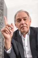 homem de meia-idade de terno ameaça seu dedo foto