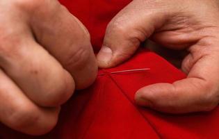 mãos costura com agulha e linha em casa foto