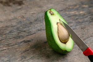 abacate fresco cortado ao meio em uma placa de madeira com fundo de faca foto